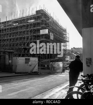 GLASGOW, SCOTLAND - NOVEMBER 2nd 2018: A black and white photograph of a man leaning on a wall while workers work on the site of Glasgow School of Art - Stock Photo
