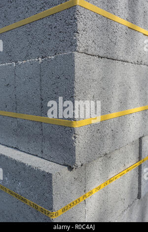 Stack of cinder blocks on a new-build housing site. Supplier'sdetails on bottom yellow band, hence RM - but guess could be erased where required. - Stock Photo
