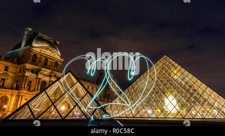 Paris, France - September 30, 2018: Abstract light painting of two hearts with background of bright pyramids of Louvre museum at night. - Stock Photo