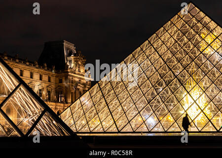 Paris, France - September 30, 2018: Bright light glass pyramids with silhouette walking people of Louvre museum at night. - Stock Photo