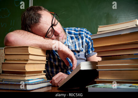 Tired and tortured disheveled student in glasses is sleeping at the table on a stack of books against the background of the chalkboard. - Stock Photo