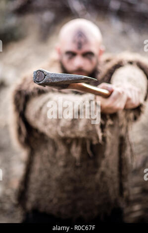 A male viking inspired character in the mountains. Model wearing real fur and carrying an axe - Stock Photo
