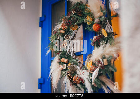 Modern christmas wreath with oranges,herbs, rustic ornaments, pine cones, branches on blue door in european city street. Festive decorations and illum - Stock Photo