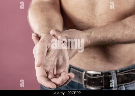 Close up of man suffering from pain in his wrist - Stock Photo