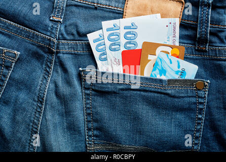 One hundred Turkish Lira bills and credit cards in the back pocket of a blue jean. - Stock Photo
