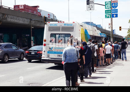 People waiting in queue on the public bus station to get on the bus in Montreal, Quebec, Canada. - Stock Photo