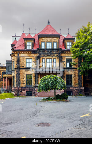 Old classy historical victorian house facade with stone wall in Montreal, Quebec, Canada. - Stock Photo