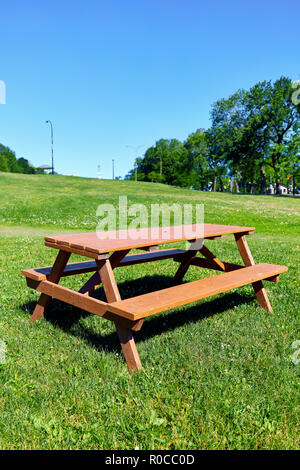 Wooden picnic bench on a green grass field in the park on a sunny summer day - Stock Photo