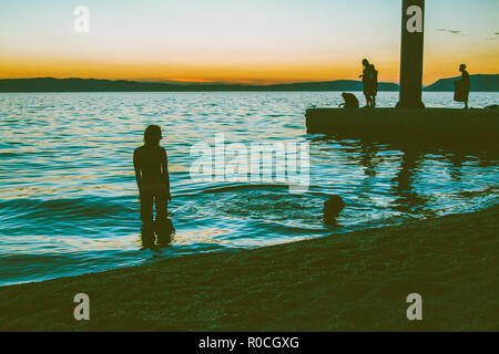 Cres, Croatia, lighthouse in sunset, seascape, summer evening, people on the beach, enjoying list moments of the day - Stock Photo