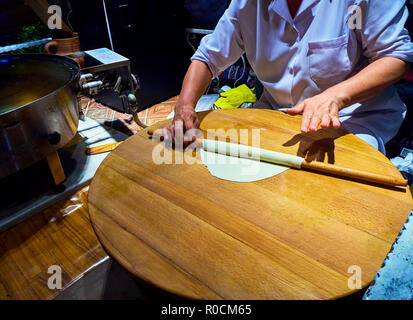 A cook making Turkish Gozleme, a traditional Anatolian stuffed flatbread, cooked over a wood fire on a griddle. - Stock Photo