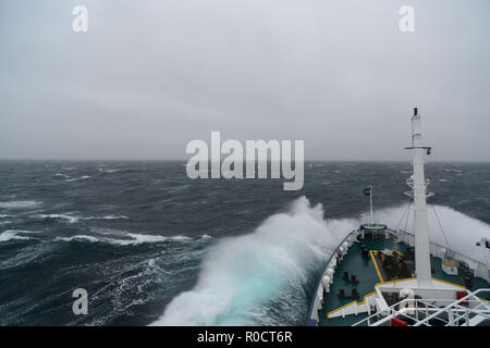 Ship cruising in storm and heavy seas crossing the Denmark Strait between Greenland and Iceland. - Stock Photo