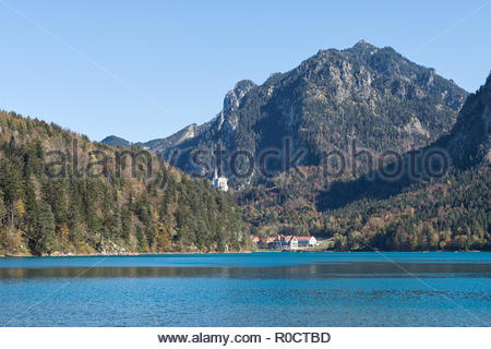 View from the path around Lake Alpsee, Füssen,  to Tegelberg, Neuschwanstein Castle and café Alpenrose am See with the newly built hotel in autumn. - Stock Photo