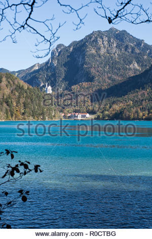 View from the path around the Lake Alpsee, Füssen,  to the lake, mountain Tegelberg, Neuschwanstein Castle and café Alpenrose am See, in autumn. - Stock Photo