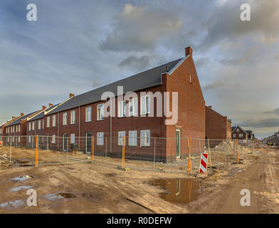 New completed young family houses on a builing site with unpaved roads in Randstad, Netherlands - Stock Photo