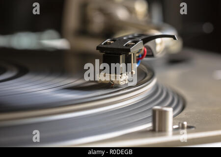 Close up of a turntable needle head playing music from an lp - Stock Photo