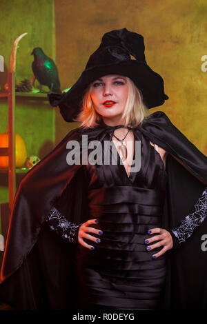 Photo of smiling witch in black hat, dress - Stock Photo