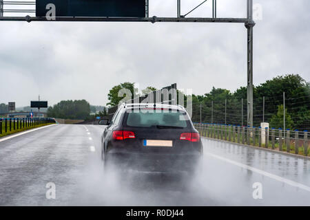 A car on a wet road in the rain. View from the rear through the car window. - Stock Photo