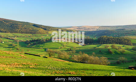 Under deep blue sky, long-distance picturesque view to Wharfedale (rolling hills & green pasture in sunlit valley) - Yorkshire Dales, England, UK. - Stock Photo