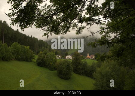 Alpine mountain landscape with typical houses and small church surrounded by lush meadows and dense forest - Stock Photo