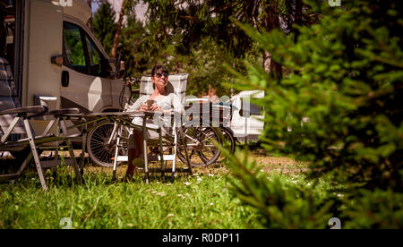 Woman with a mug of coffee near the camper. Caravan car Vacation. Family vacation travel, holiday trip in motorhome RV - Stock Photo