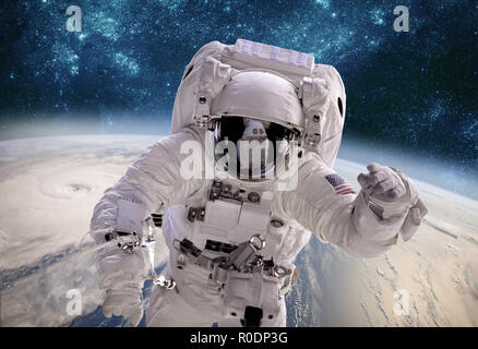 Astronaut in outer space against the backdrop of the planet earth. Typhoon over planet Earth. Elements of this image furnished by NASA. - Stock Photo