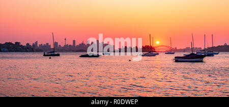 Sydney Australia. A beautiful sunset over Sydney Harbour Bridge reflected in the tranquil waters of Hermit Bay in Vaucluse. - Stock Photo