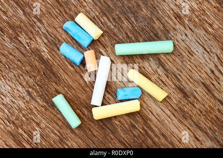 Several cylindrical pieces of colorful chalk on the old eroded brown board - Stock Photo