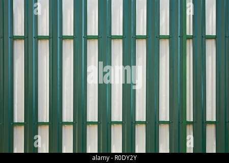 Rear side of the new metal fence of white and green tints in daylight as texture - Stock Photo