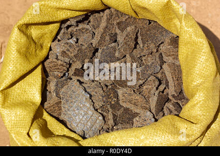Pieces of sunflower seed cake in expanded sack close up. It is used as feed for animals, birds and fish - Stock Photo