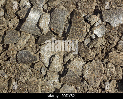 Shapeless pieces of oil cake in the heap close up. It is used as feed for animals, birds and fish - Stock Photo