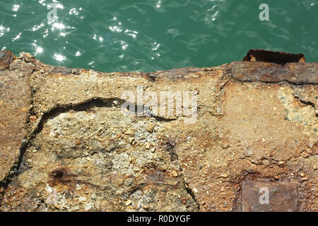 Detail of old reinforced concrete pier over the water in a bright sunlight - Stock Photo