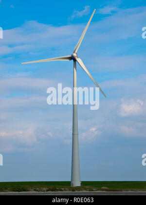 Wind turbine lightened up by sunbeam - Stock Photo