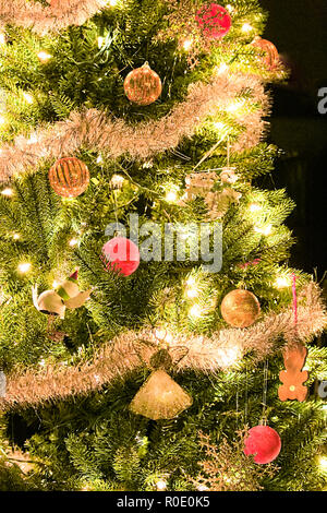A the side of a decorated christmas tree shining in the dark - Stock Photo