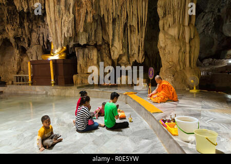 KANCHANABURI, THAILAND, JANUARY 19, 2016 : A thai family is praying and meditating with a Buddhist monk in the Wat Tham Pu Wa cave temple in Kanchanab - Stock Photo
