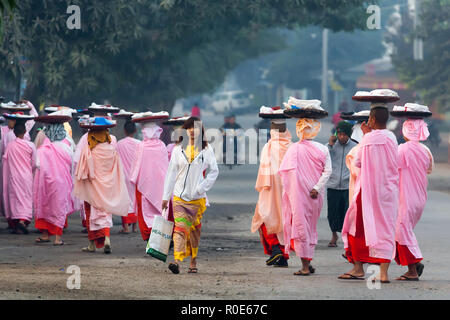 BAGAN, MYANMAR, JANUARY 25, 2015 : A row of Buddhist nuns carrying plates on head for morning alms is walking in the streets of Bagan in Myanmar (Burm - Stock Photo