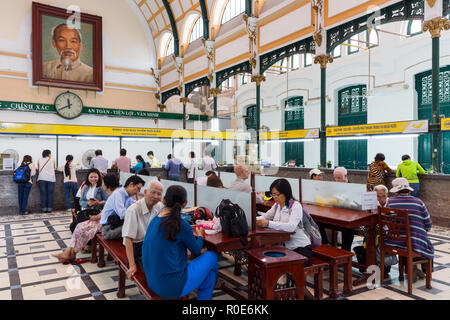 HO CHI MINH (SAIGON), VIETNAM, DECEMBER 08, 2014 : Customers are preparing packages and letters in the french colonial central post office in Saigon,  - Stock Photo