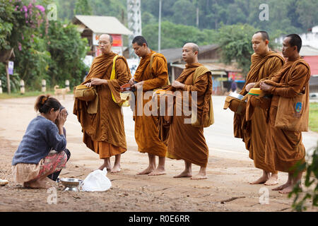 PHANG MAPHA, THAILAND, NOVEMBER 19, 2012: women giving daily food at the Buddhist monks during early morning traditional alms in the village of Phang  - Stock Photo