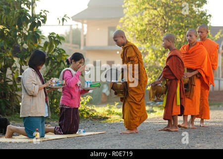 VANG VIENG, LAOS, MARCH 19, 2011: women giving daily food at the Buddhist monks during early morning traditional alms in the village of Viang Vieng, L - Stock Photo