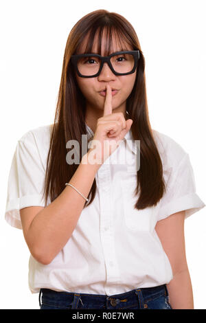 Young cute Asian teenage girl with finger on lips  - Stock Photo
