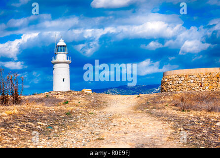 Beautiful landscape with lighthouse, old road and cloudy sky. Paphos Archaeological Park. - Stock Photo