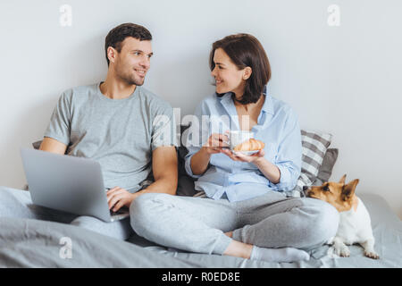 Portrait of lovely couple sit together on bed, use laptop computer, have pleasant conversation between each other, do shopping online. Jack russell te - Stock Photo