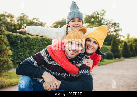 Horizontal portrait of family members spend free time together, embrace, encourage each other, have fun. Little smiling girl feels happiness, embrace  - Stock Photo
