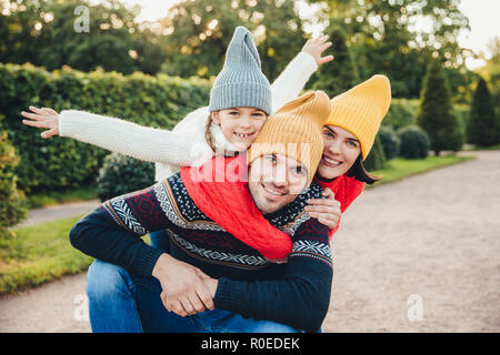 Having nice time together! Smiling excited woman, man and their little female child, wear warm knitted clothes, embrace each other, walk in park, bein - Stock Photo