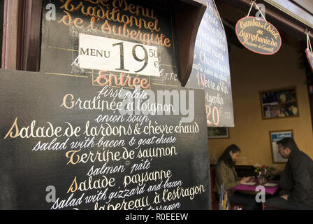 A restaurant offers a fixed-price meal (prix-fixe menu) on a sign on Rue Mouffetard, a popular street lined with cafes, bars, souvenir shops, and an o - Stock Photo