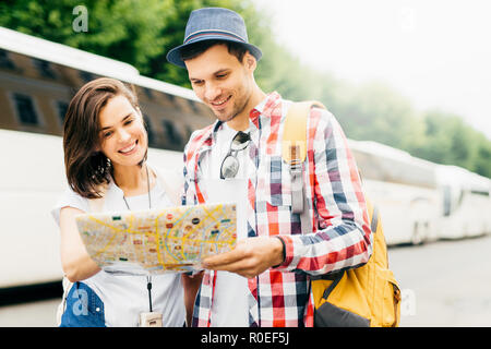 Young family tourists looking attentively in map while searching for museum in big city. Stylish man in hat and checkered shirt holding rucksack, stan - Stock Photo