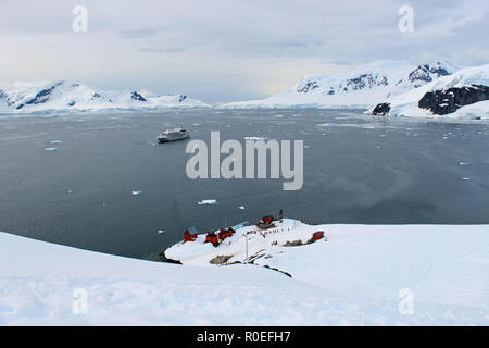 View from a peak above Paradise Bay in the Antarctic Peninsula looking down on Almirante Brown Argentine base with an expedition cruise ship at anchor - Stock Photo
