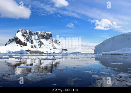 An Antarctic Expedition cruise ship at anchor amid glistening icy, reflective water of Paradise Bay in the Antarctic Peninsula on a sunny Summer's day - Stock Photo
