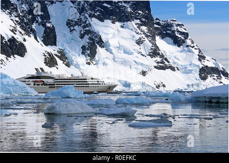 An Antarctic Expedition cruise ship at anchor amid the glistening icy waters of Paradise Bay in the Antarctic Peninsula on a sunny Summer's day - Stock Photo