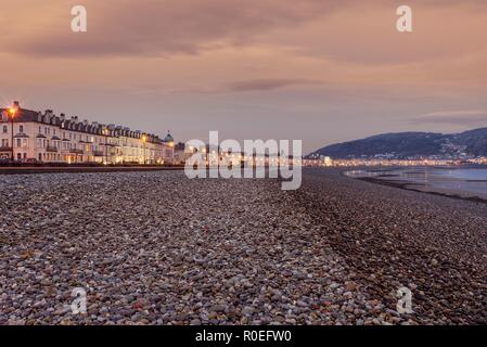 A view of Llandudno's curving shoreline lined by white fronted hotels at  sunrise. The Great Orme headland is in the distance and a dawn sky is above. - Stock Photo
