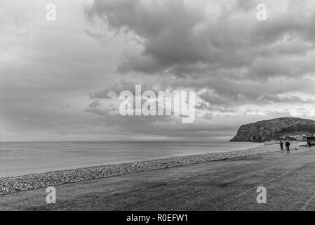 A view of Llandudno's shoreline in the early morning with people walking.  The Little Orme is in the distance and a dramatic sky is overhead. - Stock Photo